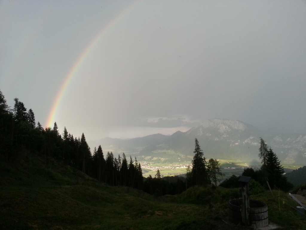 Regenbogen übers Tal von der Almhütte aus gesehen.