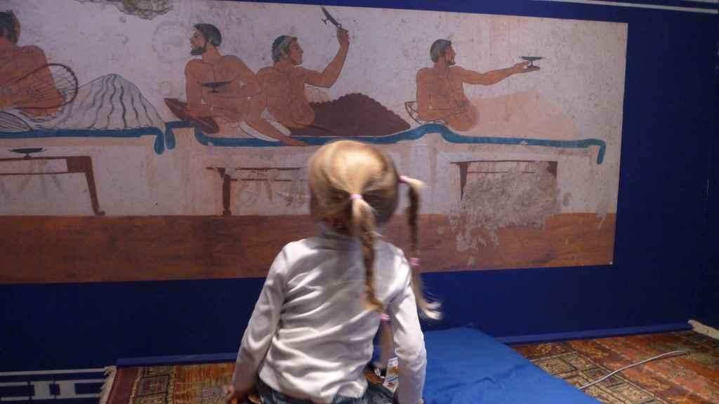 Kind ruht sich auf einer nachgebauten griechischen Ruhestätte in der Alexander-Ausstellung aus.