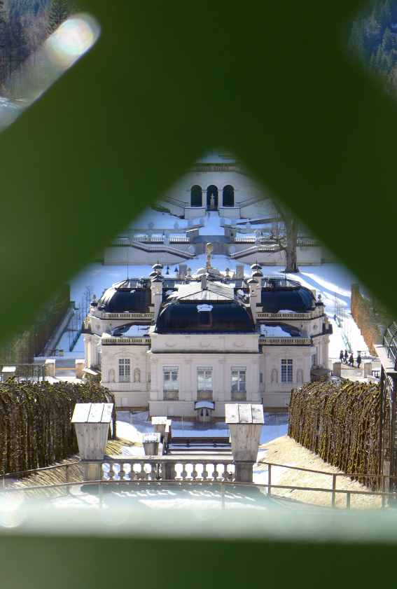 Blick durch Gitterstäbe auf das Schloss Linderhof.