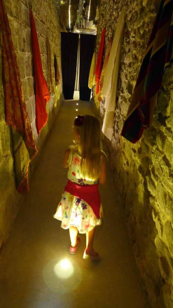 Mini geht durch einen abgedunkelten Gang. Textilien hängen zum Befühlen an den Wänden. Stia, Textilmuseum.
