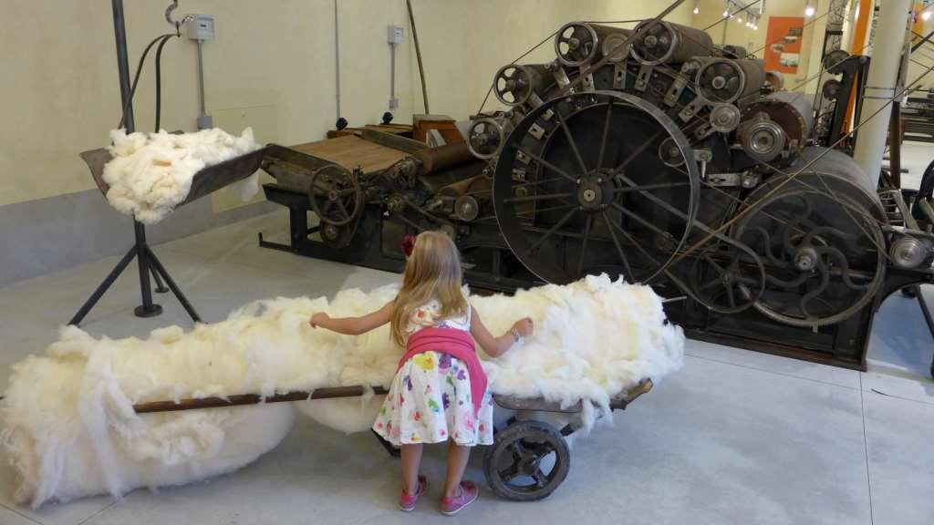Mini befühlt Wolle. Vor ihr steht eine Krempelmaschine. Stia, Baumwollmuseum
