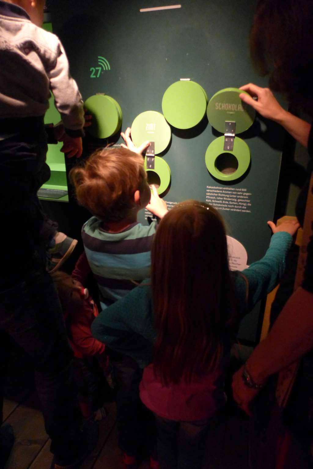 Kinder und Erwachsene stehen vor einer Duftstation in der Regenwald-Ausstellung und riechen neugierig, angewidert und überrascht.