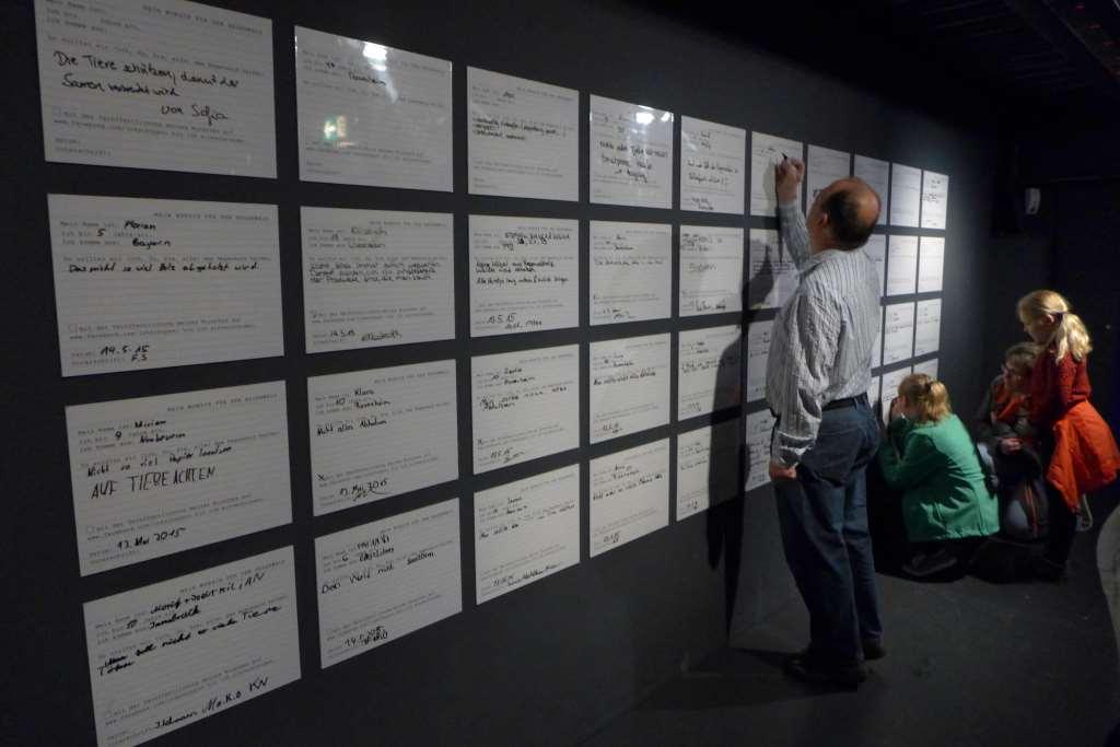 Mitmachstation - was nun? Besucher geben an einer großen Pinnwand ihre Tipps zur Rettung des Regenwaldes ab.