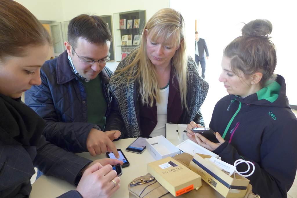 Letzte Anweisungen für den bevorstehenden Tweetwalk #lustwandeln in Schleißheim. Mitarbeiter der Schlösserverwaltung stehen um einen Stehtisch und prüfen ihre Handys.