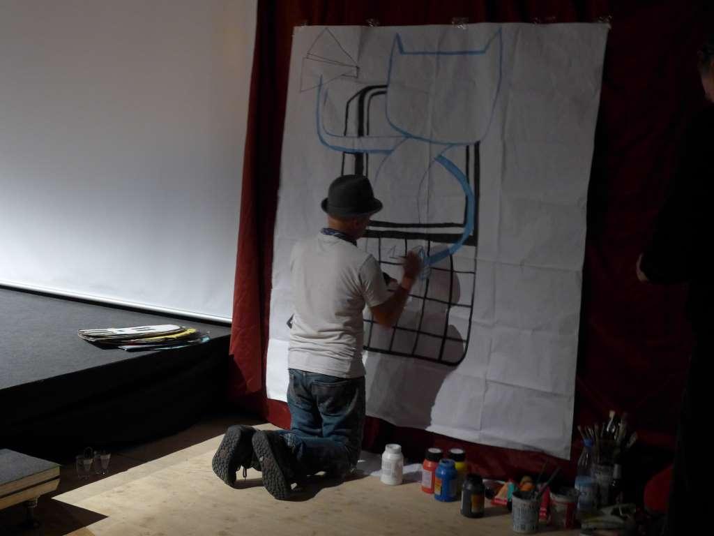Der Künstler Jim Avignon malt während der Preisverleihung ein Bild.