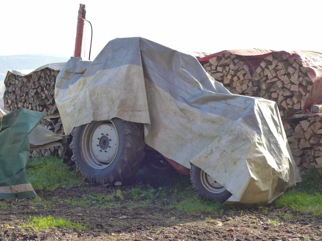 Eingepackter Traktor vor Holzstapel
