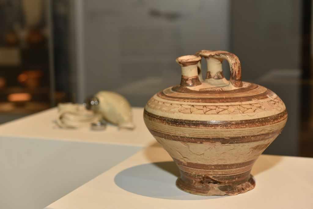 Eine mykenische Bügelkanne wird neben einen Rasier ausgestellt. Beides hat miteinander zu tun. OMG-Ausstellung.