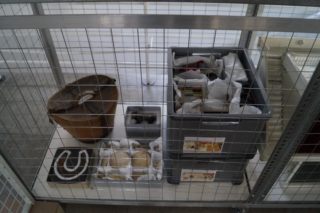 Präsentation der Depotobjekte: verpackt in Kisten und hinter Gitter. Omg - Ausstellung in Karlsruhe