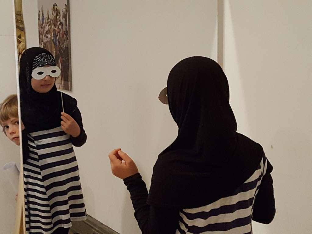 Kinder mit Migrationshintergrund machen eine Museumstour in München - hier Maskenspiel