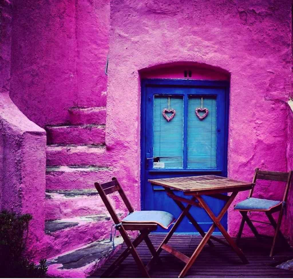 Rosaroter Hauseingang mit Tisch und zwei Stühlen davor. Das Bild steht symbolisch für die Chancen, die das Web bieten und damit für die Blogparade #webseidank von unserleben.digital
