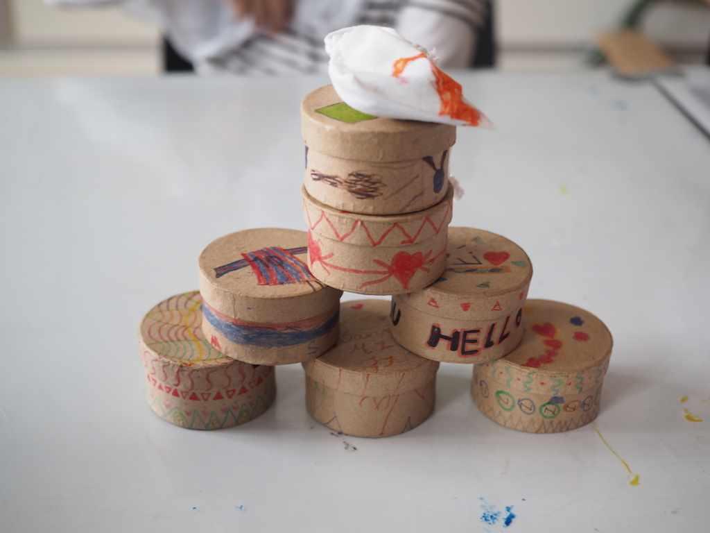 Stappel runder, bemalter Pappkistchen mit Wattebausch fürs Sorgenpüppchen darauf. Bastelmaterial im Museum Fünf Kontinente in München für die Kinder mit Migrationshintergrund #MMuseumsT
