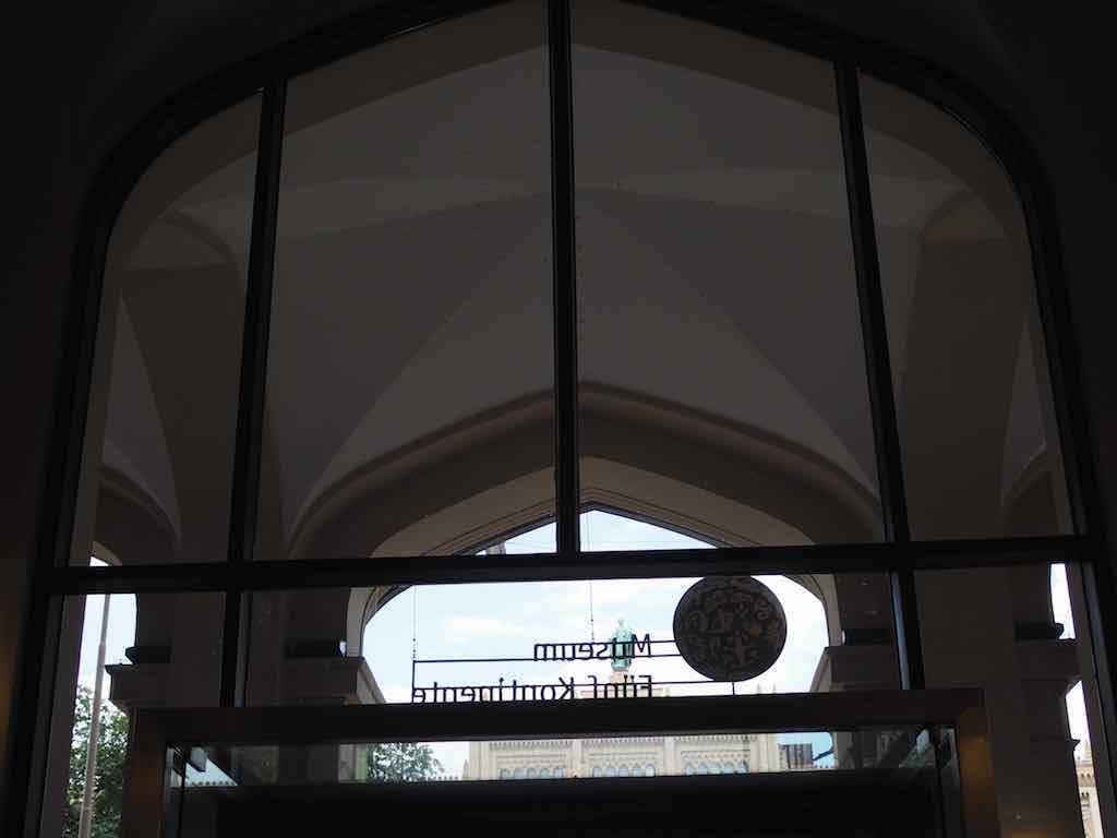 Eingang des Museums Fünf Kontinente in München von innen gesehen. Die Aufschrift des Museums ist in Spiegelschrift zu lesen. Ein Kind mit Migrationshintergrund las es ohne Schwierigkeiten bei seiner Museumstour #MMuseumsT