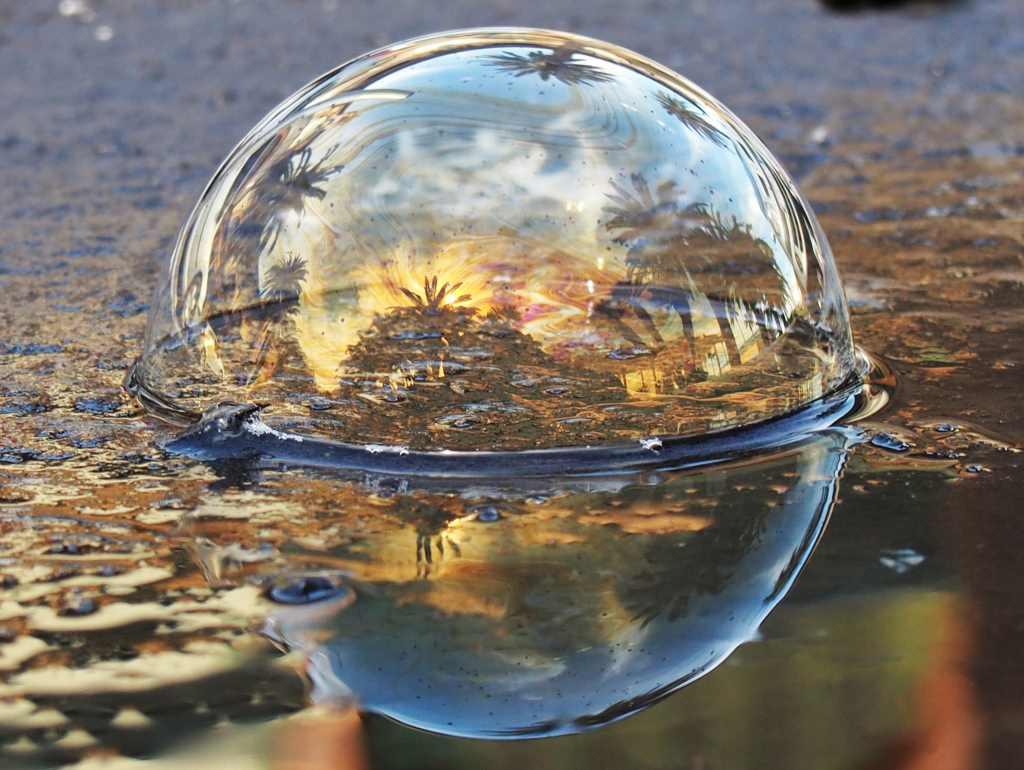 Eine große Seifenblase liegt auf dem nassen Bodern. Auf ihr spiegelt sich die Silhouette Nizzas. Arbeit vom syrischen Künstler Khaled Youssef.