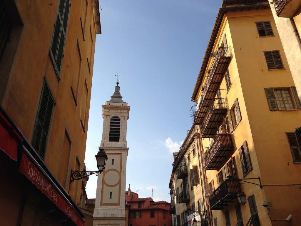 Blick auf den Kirchturm durch eine Gässchen in der Altstadt von Nizza bei strahlendem Sonnenschein.