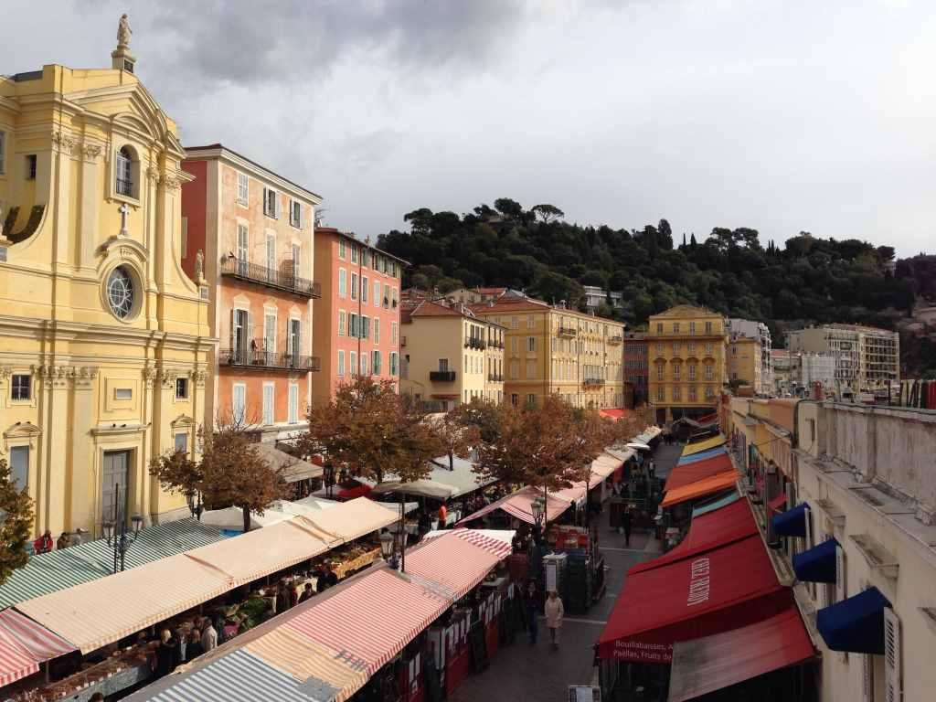Blick von oben auf die Marktstände im Cours Saleya der Alstadts von Nizza. Eine bunte Fassadenpracht, bestrahlt von der Sonne.