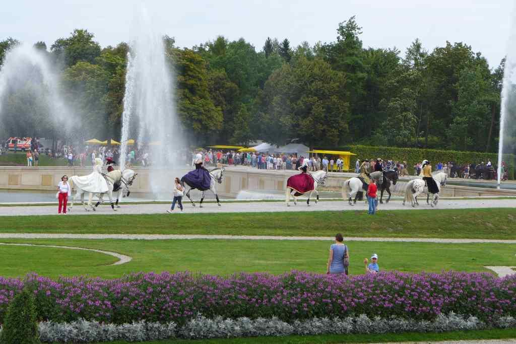 Fünf kostümierte Reiter im Barockparterre des Schlosspark Schleißheims vor einer der Fontänen.