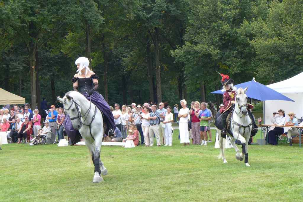 Reiterinnen in historischen Barockgewändern zeigen ihre Reitkünste im Schlosspark Schleißheim.