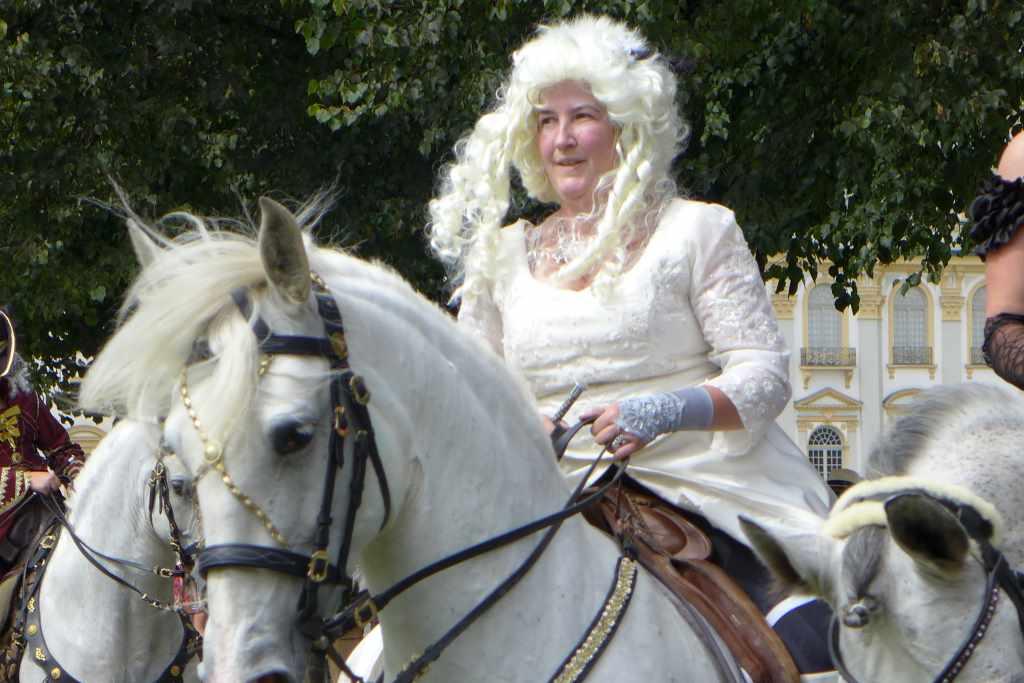 Detailansicht von einer älteren Reiterin im Barockgewand.