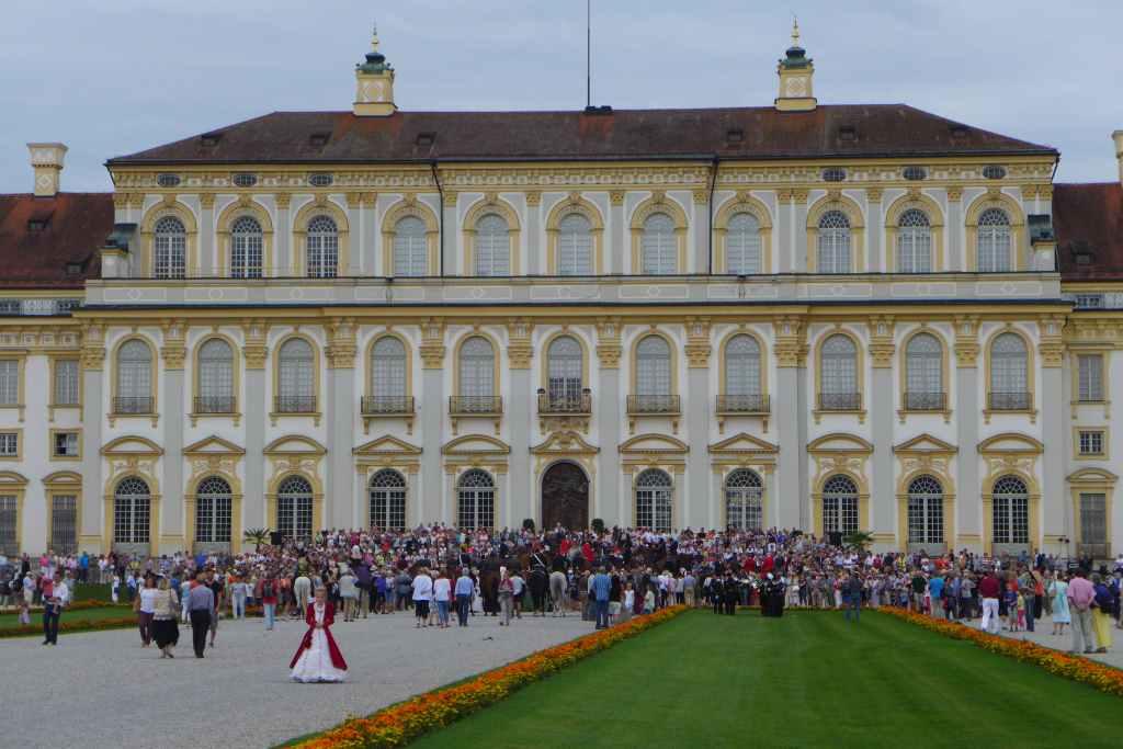 Das Neue Schloss Schleißheim von der Gartenseite mit Menschenauflauf vor der Gartenterrasse. Kostümierte und Kutschen werden vorgestellt.