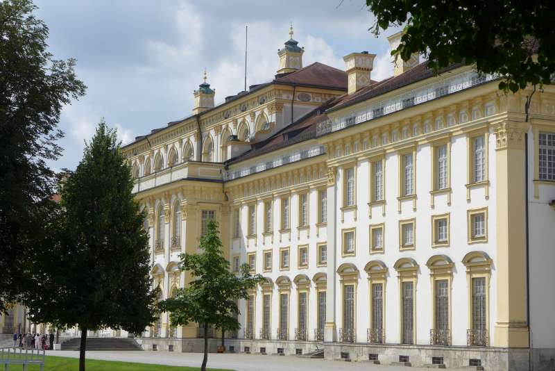 Blick vom Garten aus auf das Neue Schloss Schleissheim. Bäume stehen davor.
