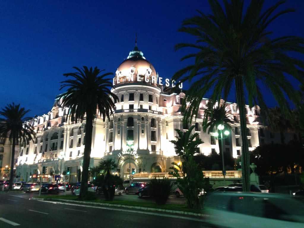 Blick bei Dämmerung auf die Fassade des beleuchteten Hotel Negresco in der Neustadt von Nizza