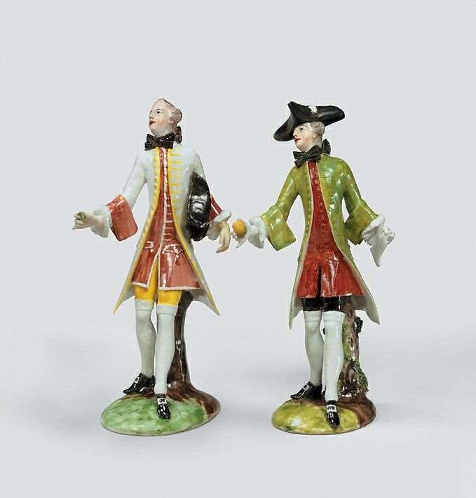 Zwei Porzellanfiguren aus dem Tafelaufsatz von Franz Anton Bustelli, ausgestellt im Bayerischen Nationalmuseum. Die höfischen Herren tragen Kniebunthosen, einer hält eine Zitrone in der Hand und hat einen Dreispitz auf dem Kopf. u