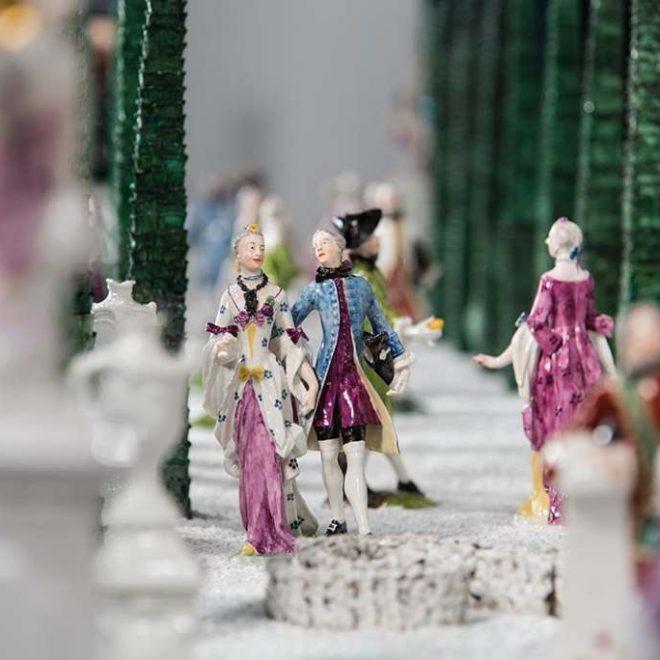 Blick in den Lustgarten en miniture aus Nymphenburger Porzellan. Figurenpaare, einzelne Porzellanfiguren wandeln anmutigt durch den Barockgarten. Franz Anton Bustelli schuf den Tafelaufsatz im Bayerischen Nationalmuseum München.