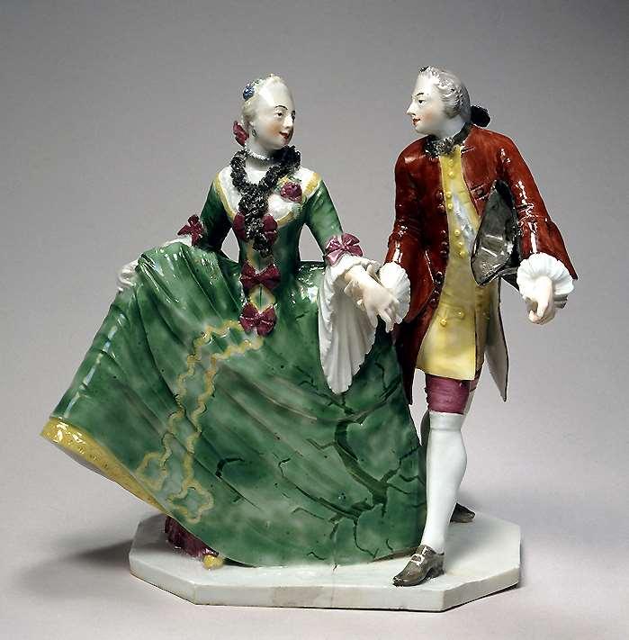 Das Figurenpaar aus Nymphenburger Porzellan zeigt eine höfische Dame, deren Hand von ihrem Galan gehalten wird. Sie rafft ihren grünen Rock hoch und schaut ihn verliebt an. Porzellanfiguren aus einem Tafelaufsatz im ayerisches Nationalmuseum