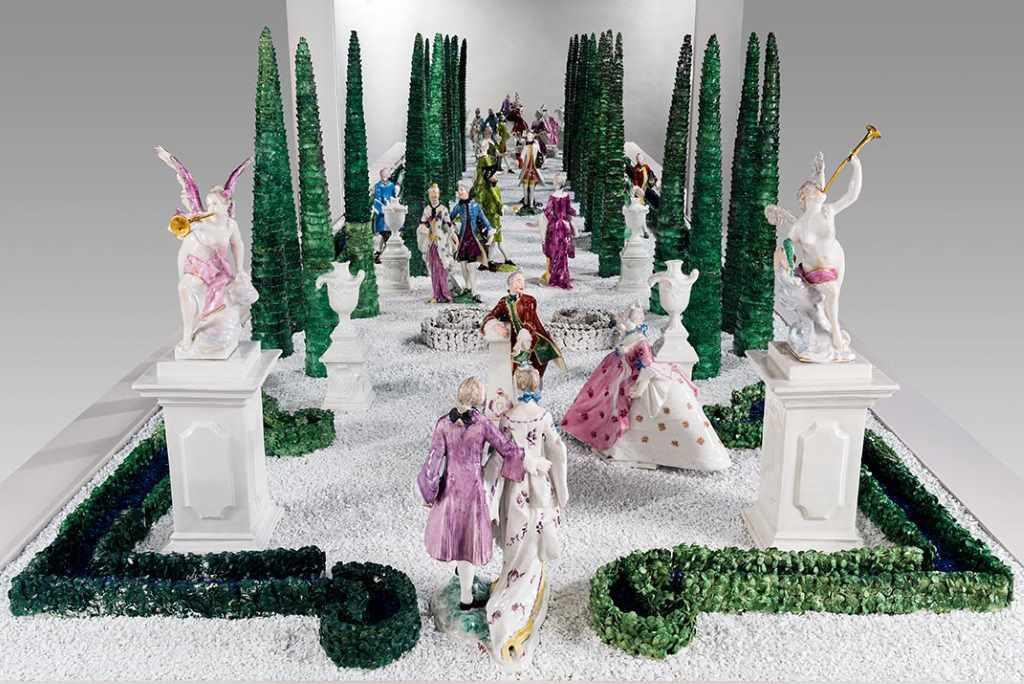 Hecke und Porzellanfiguren aus Tafelaufsatz in Form eines barocken Lustagartens mit Figurenpaaren in höfischer Gewandung, Bäumen, Postamenten. Nymphenburger Porzellan gefertigt von Franz Anton Bustelli, ausgestellt im Bayerischen Nationalmuseum in München.