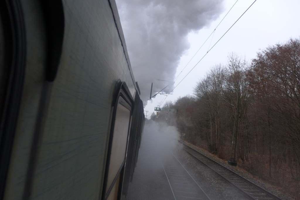 Blick aus dem Zug zur dampfumwolkten Dampflok 01 2066-7 während der Fahrt.  Historische Dampfzugfahrten.
