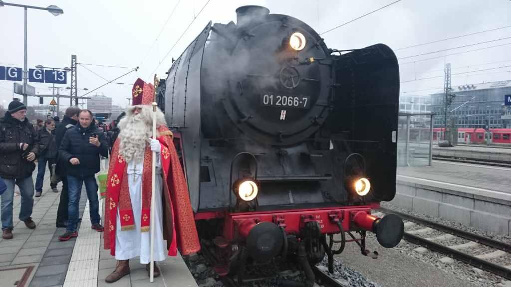 Nikolaus steht vor der Dampflok 01 2066-7, die von Erwachsenen umlagert wird. Historische Dampfzugfahrten