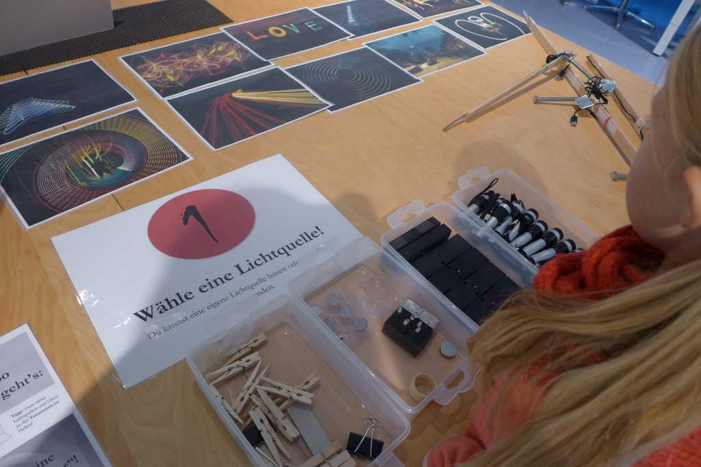 Mädchen betrachtet auf dem Tisch liegende Anweisungen, um mit Licht zu malen in der offenen Experimentierwerkstatt im Deutschen Museum. #Mustip Museum mit Kindern in München entdecken.