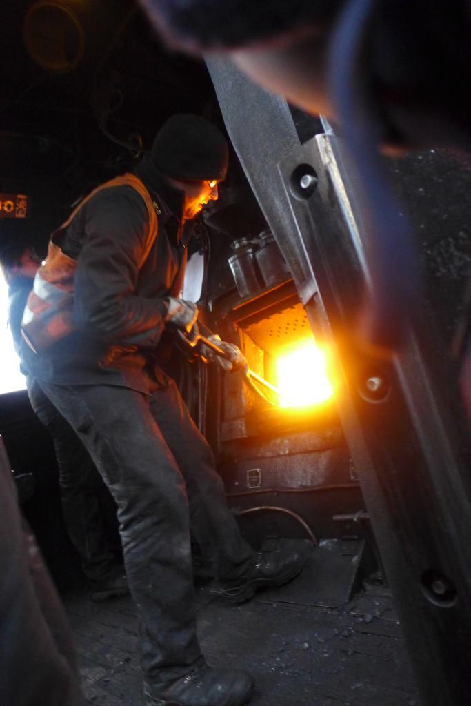 Blick in den Führerstand der Dampflok 01 2066-7. Der Heizer befeuert den Kohlekessel. Historische Dampfzugfahrten