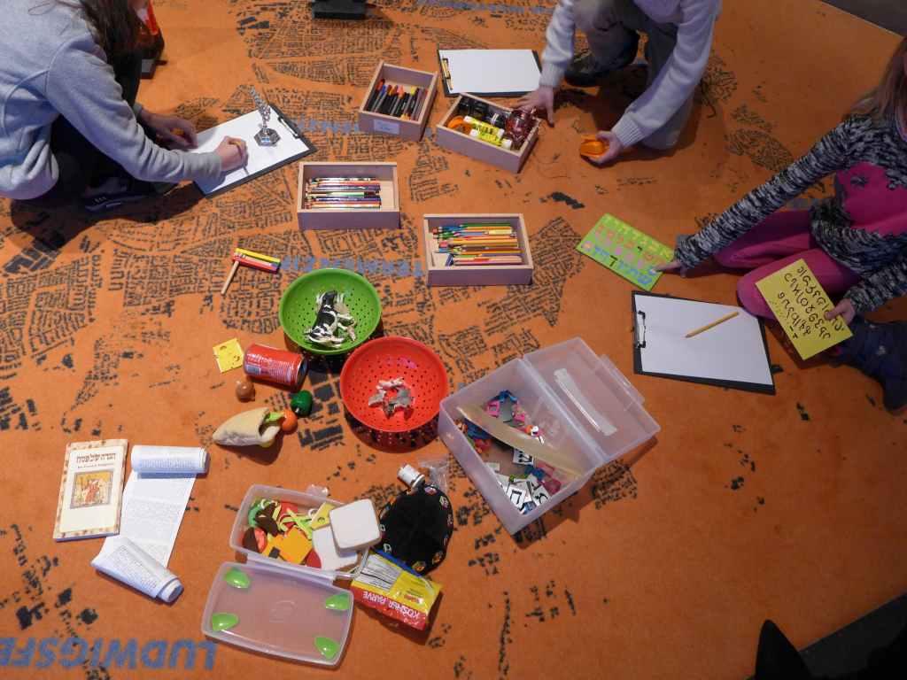 Spielerisch wird den Kindern bei der Führung im Jüdischen Museum München jüdisches Brauchtum vermittelt. Auf dem Boden liegen ausgebreitet Stifte, Tiere und Papier. #MusTipp