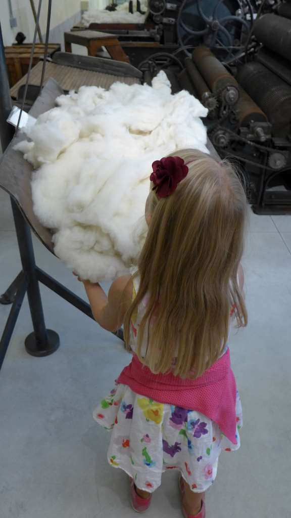 Mädchen steht mit dem Rücken zum Betrachter, die Arme vergraben in Schafswolle im Textilmuseum in Stia, Toskana. #MusTipp