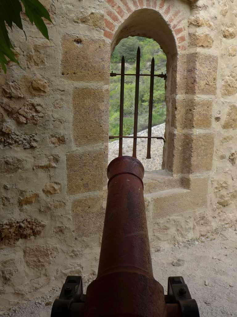Alte, verrostete Kanone ist auf vergitterte Fensteröffnung gerichtet. Sie befindet sich in der Festung Forte Libéria et Cité de Villefranche in Südfrankreich. #KultTrip mit Kulturreisen.