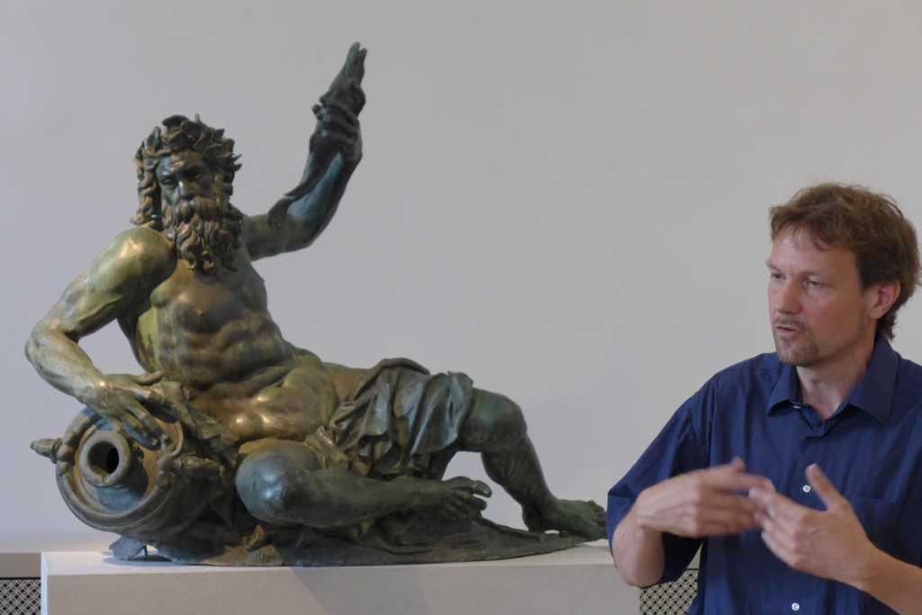 Dr. Christian Quaeitzsch, Museumsreferent der Residenz München, steht vor einem Flussgott in der Bronzesammelung der Residenz München und erklärt die Besonderheiten des Sammlungsbestandes während des Tweetups #BronzeBreak, das StudentInnen der Kunstgeschichte der LMU organisierten.