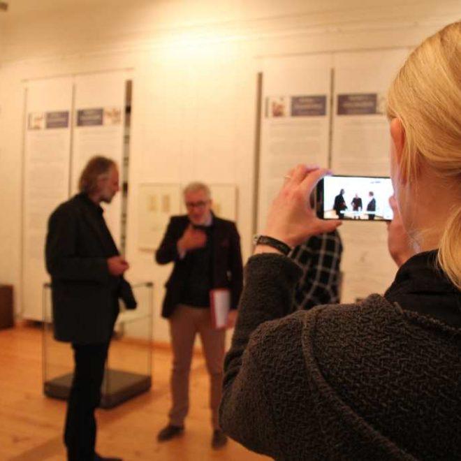 Rückenansicht einer Frau mit Smartphone in der Hand, die im Museum Burg Posterstein in der Ausstellung den Direktor im Gespräch mit jemandem fotografiert. Warum Social Media und Bloggen im Museum beantwort Marlene Hoffmann von Burg Posterstein im zweiten Montagsinterview auf Kultur-Museum-Talk.