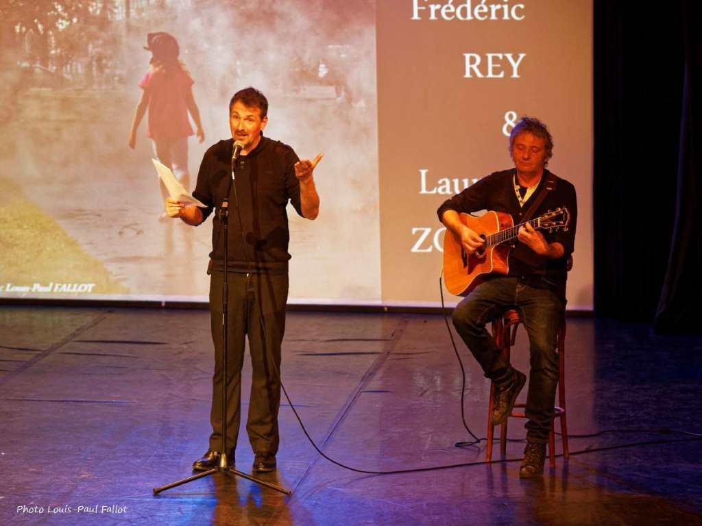 Zwei Männer auf der Bühne, der eine, Frédéric Rey, trägt ein Gedicht vor, der andere, Laurent Zoppis begleitet ihn mit der Gitarre.