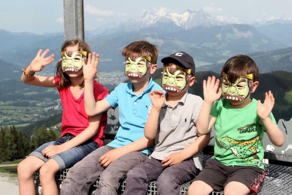 Vier Kinder mit Masken sitzen vor einer Bergkulisse. Das Foto ist Titelbild zum Montagsinterview mit KiMaPa - dem Familienportal in München und Umgebung.