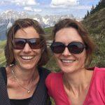 Zwei lachende Frauen vor Bergkulisse. Isabella und Layla schreiben auf KiMAPa - dem Familienportal rund um München - über ihre Ausflüge, vermitteln Tipps und Tricks für Kinder. Montagsinterview