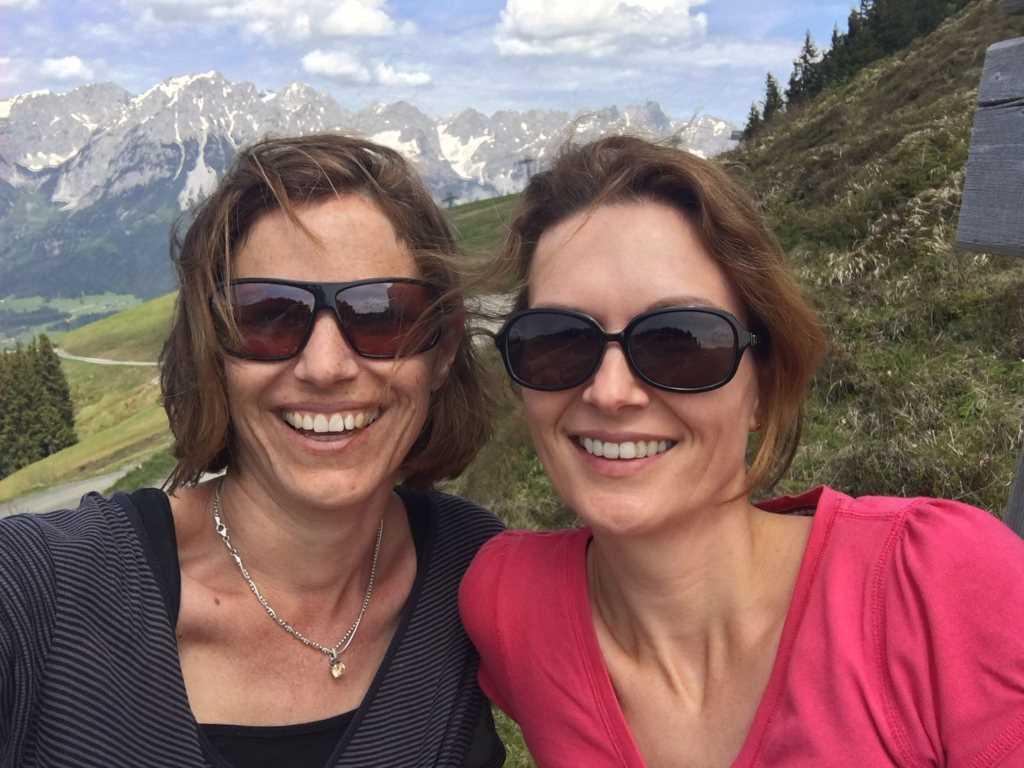 Zwei lachende Frauen vor Bergkulisse. Layla und Isabella schreiben auf KiMAPa - dem Familienportal rund um München - über ihre Ausflüge, vermitteln Tipps und Tricks für Kinder. Montagsinterview