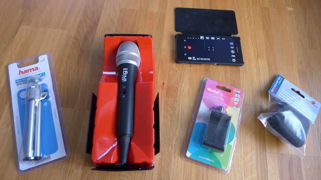 Bild mit technischen Geräten in Verpackung zum Fotografieren und Filmen mit dem Smartphone: Microphone, Handy mit geöffneter Filmeapp etc.