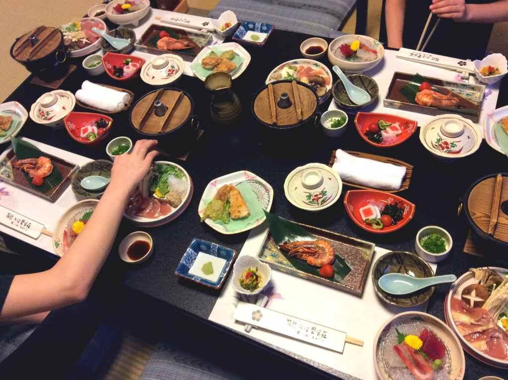 Bunt gedeckter Tisch mit japanischen Speisen in einem Ryokan. Hand greift nach essen. Reisen mit Kindern, Montagsinterview