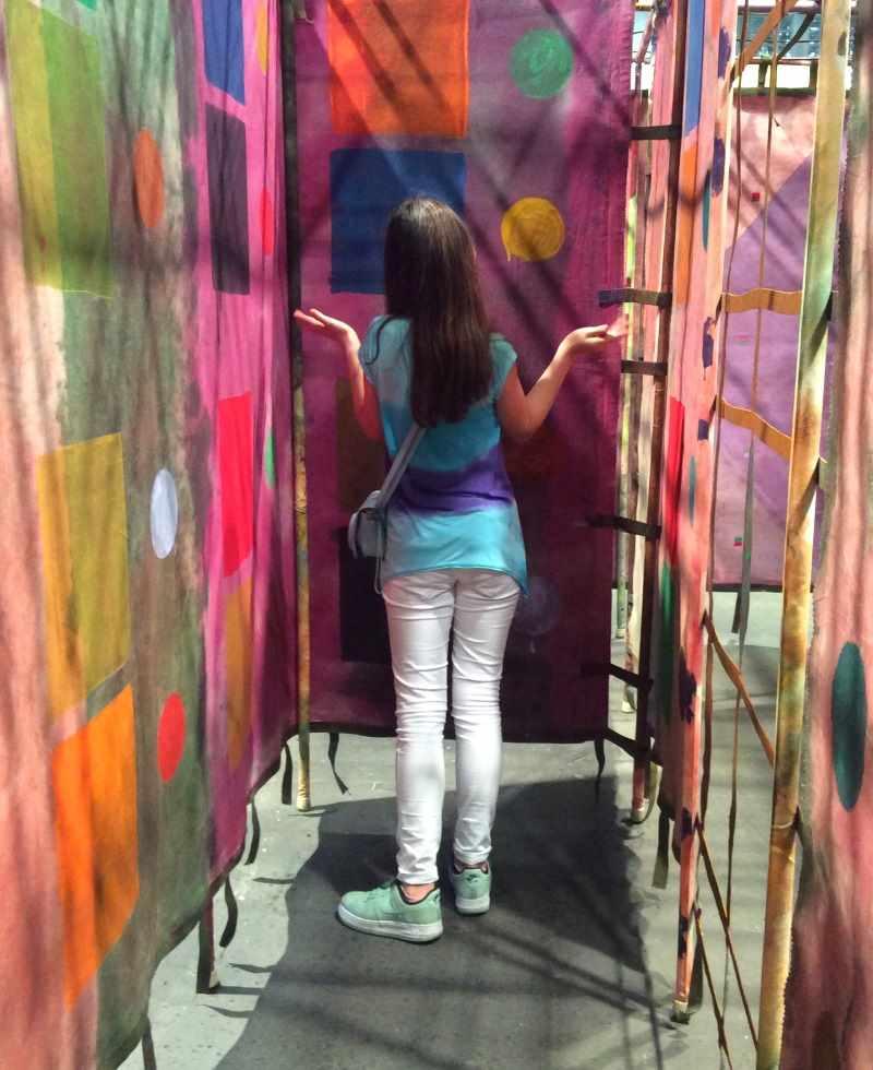 Mädchen in einer grell-bunten, mit Tüchern herunterhängenden Rauminstallation von Alan Shield Textillabyrinth auf der Art Basel 2016. Reisen mit Kindern.