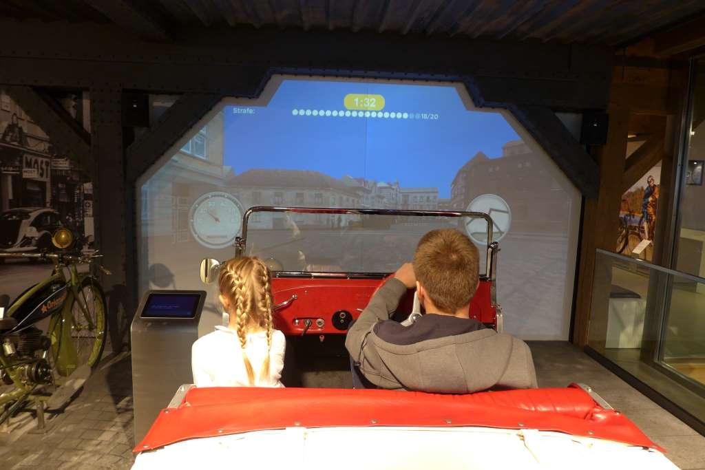 Zwei Kinder sitzen in einem offenen Cabrio im PS Speicher Einbeck und simulieren eine Autofahrt. Social Media im Museum