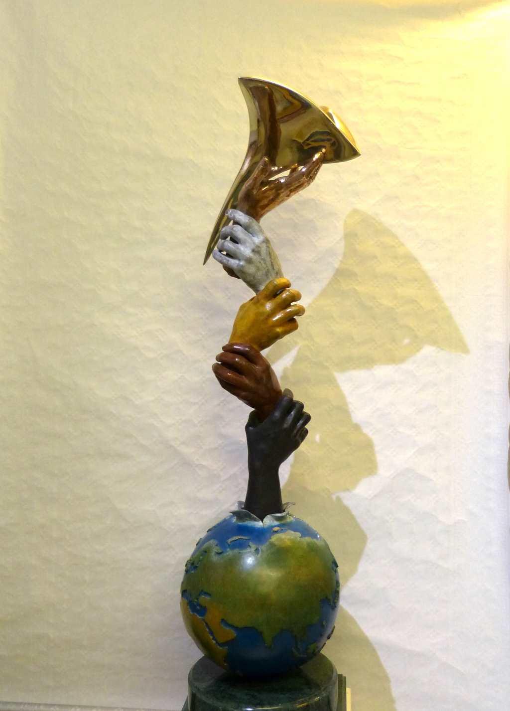 Skulptur von Michel Anthony: Unity Liberty. Weltkugel, Hände halten sich.