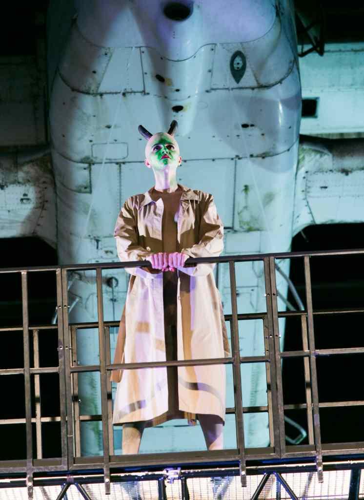 """Beleuchteter Teufel vor dem Rumpf eines Flugzeugs. Bühnenbild und Szenenfoto von """"Flight"""" der Theaterakademie August Everding in München."""