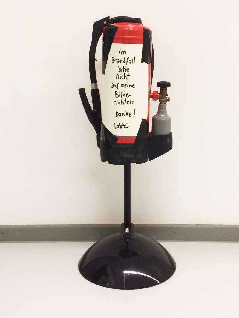 """Ein Feuerlöscher mit der Aufschrift """"Im Brandfall bitte nicht auf meine Bilder richten. Danke, Laas"""". Das Kunstwerk von Laas Abendroth steht zur fiktiven Auktion frei. Warenhauskunst in der Ludwiggalerie Schloss Oberhausen"""