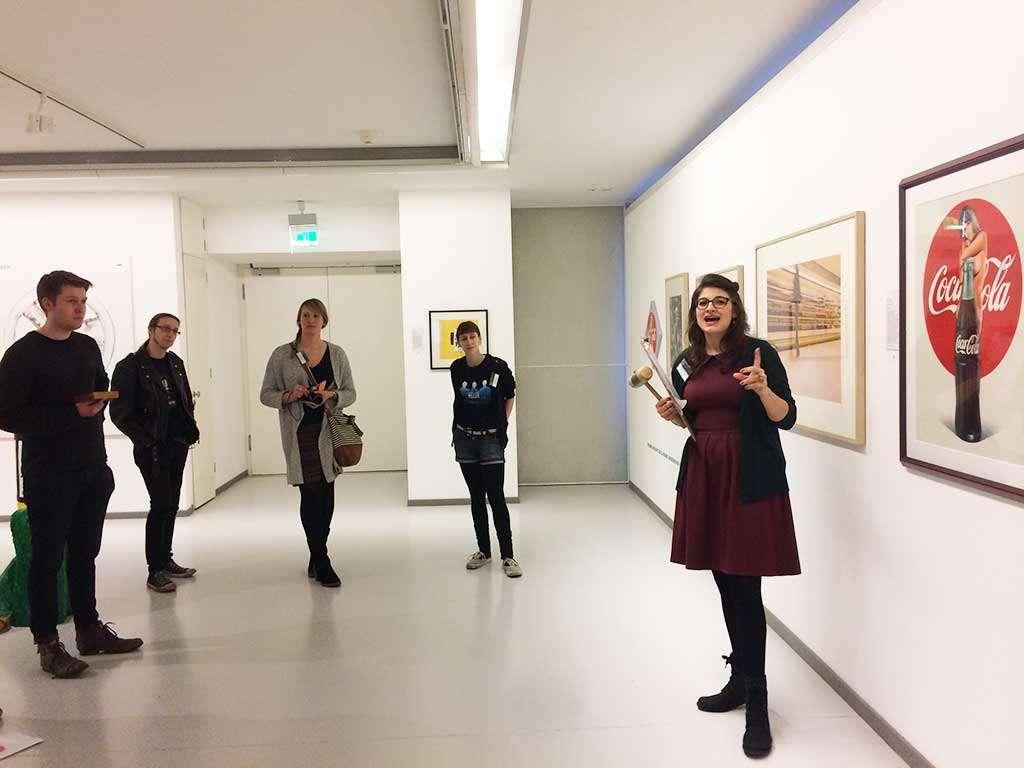 """Vier Blogger lauschen Linda Schmitz bei der fiktiven Versteigerung von Mel Ramos """"Lola Cola"""" bei der Aktion Warenhauskunst der Ludwiggalerie"""
